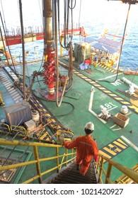 An engineer walks down steep stairway from jack up rig to wellhead platform main deck where BOP is installed.