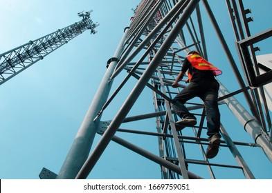 engineer wear safety equipment climb high tower for working telecom maintenance.