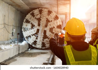 Engineer wear yellow helmets,vests  safety are discussing.Technician control underground tunnel construction at working shaft.Transport pipeline by Tunnel Boring Machine(TBM) method for electric train