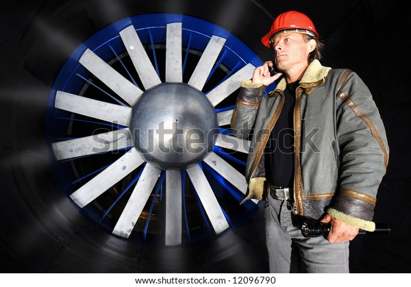 An engineer, wearing a coat and a hardtop, making a telephone call in front of the huge blades of a wind tunnel rotor