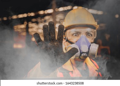 Engineer wearing a gas mask on his face working in industrial factory and show hand for stop.worker engineer industry.engineer workplace in industrial company with mechanical engineering.