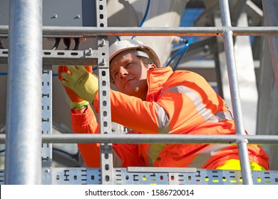 Engineer wearing hi viz protective clothing working on construction site of cement processing plant