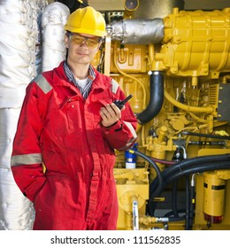 Engineer, wearing overalls, hard hat and safety goggles, posing in front of a huge hydraulic engine, holding a wireless communication device in his hand