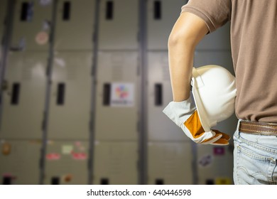 Engineer wearing a white helmet and safety gloves for workers security with blurred  locker background
