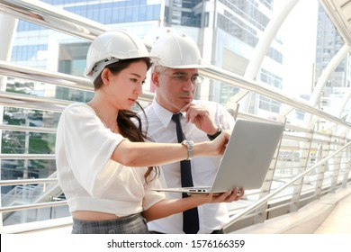 Engineer wearing white safety helmet using a laptop together, senior man and beautiful young woman discussing about project work while walking of inspection on the way outside office in downtown city