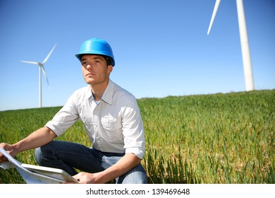 Engineer in wheat field checking on turbine production
