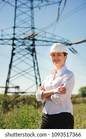 Engineer with white hard hat under the power lines. Engineer work at an electrical substation.