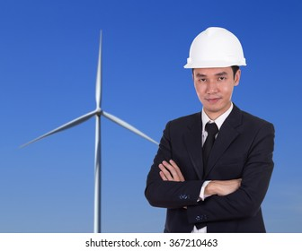 engineer in white helmet with arms crossed, wind turbine background