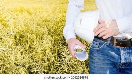 Engineer with white helmet and drawings in hand close-up. builder against background of yellow field. geologist or geodesist is exploring soil. Designer at construction site. Soil scientist