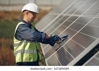 Engineer in a white helmet. Man near solar panel.