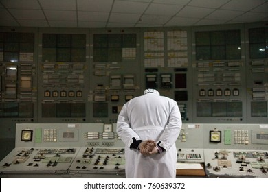Engineer in a white lab coat looking at the control panel in a control room of the industrial plant. Back view.