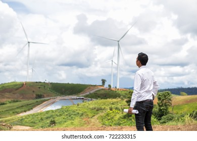 Engineer in Wind Mill Power Generator Station with  wind turbines on background