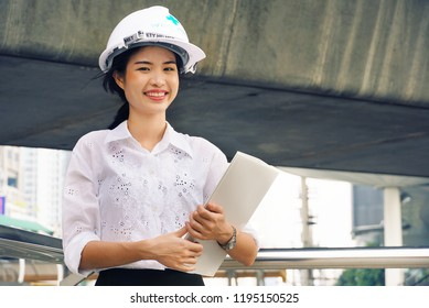 Engineer woman with helmet safty and plan design stand at construction site working