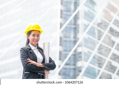 engineer woman hold blue print architects at construction site or building site of highrise building.working woman concept