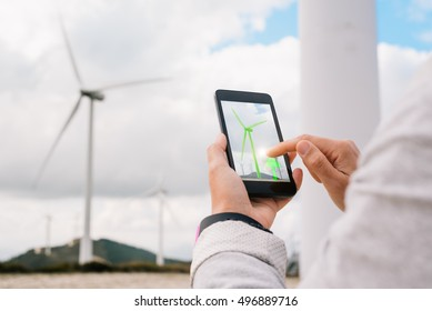 Engineer woman managing energy production app touching phone screen at wind turbine farm park generation with air flow spinning blades. Clean renewable green wind power concept.