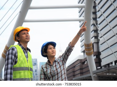 Engineer woman point finger to the air and a man in safety vest is looking to the same angle at the working area .