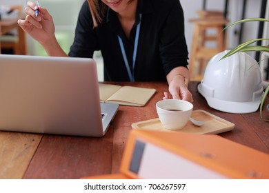 Engineer woman safety helmet on architect ,engineer working table with modern building in office  Working in coffice concept