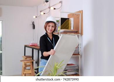 Engineer woman safety helmet on architect ,engineer working table with modern building in office  PaperWorking in coffice concept