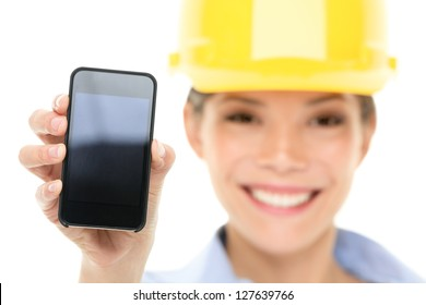 Engineer woman showing smart phone wearing construction hard hat. Young female mixed race Asian / Caucasian female professional isolated on white background.