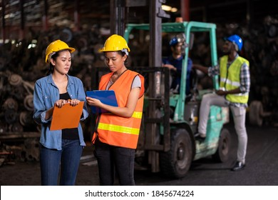 Engineer woman wearing helmet standing at the large warehouse where keep automotive parts and holding clipboard. Used of vehicle part for recycling in the scrap yard garage. Reuse and recycle concept