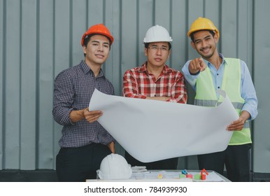 Engineer and worker checking plan or blueprints on construction site and   pointing for inspection Construction Concept