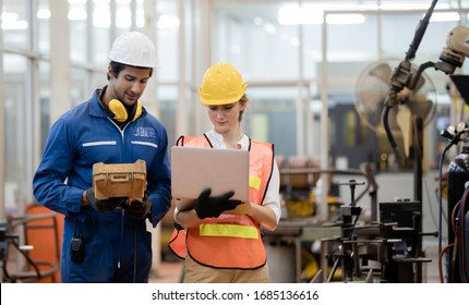 Engineer and worker control and check robot working in factory. The worker is controlling the robot to work in the factory.