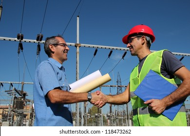 Engineer and Worker at Electrical Substation. Smiling workers with blueprints and clipboard in meeting at electrical substation. Electrical power industry. Electric power distribution