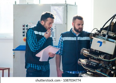 The engineer and the worker are examining the machine