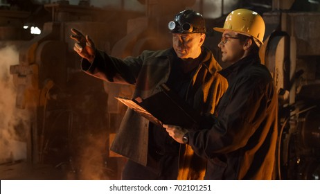 Engineer and Worker Have Conversation in Foundry. Rough Industrial Environment. Middle Shot.