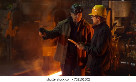 Engineer and Worker Have Conversation in Foundry. Engineer Using Tablet. Rough Industrial Environment.