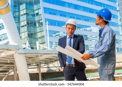 Engineer and worker with helmet looking paper plans at construction site.