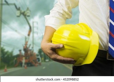 engineer or worker hold in hand yellow helmet  discussing blueprint next to electrical substation for workers security in front of construction blur background.vintage tone