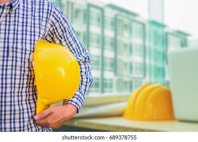 engineer or worker holding in hand helmet for workers security on cityscape background