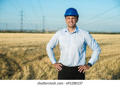 engineer or worker smiles in protective helmet holding a phone. Wheat field, power line, sunny day, blue sky.