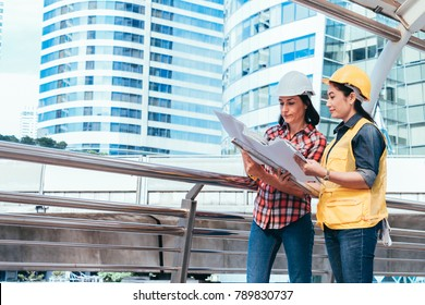 Engineer and worker team with helmet looking paper plans at construction site.