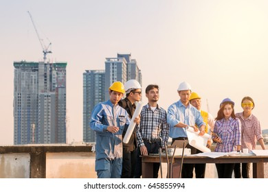 Engineer and worker team talking about project with construction site and cityscape background.