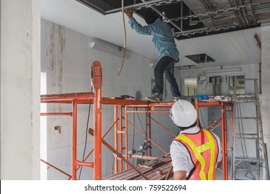 The engineer  at worker is working on high level of scaffold which not have line guard for protect him fall to the ground and he does not wear helmet and vest