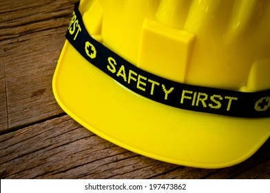 Engineer or Worker Yellow Safety Helmet Hat with SAFETY FIRST word tag on Wood background, Rustic Style / Concept for Carpentry Carpenter Work.