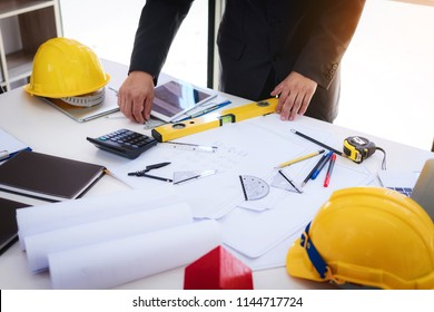 engineer  working  at a drawings of house in office for discussing. Engineering tools and construction concept.
