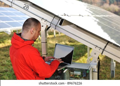 Engineer working with laptop by solar panels
