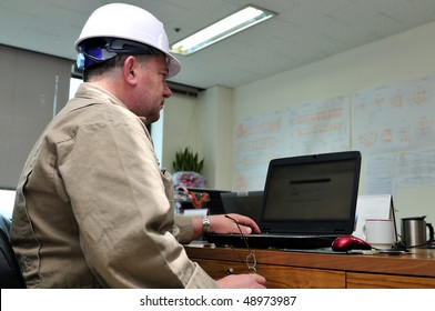 Engineer, working with laptop in office