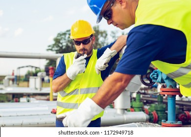 Engineer working in a oil refinery with talking on the portable radio for controlling work