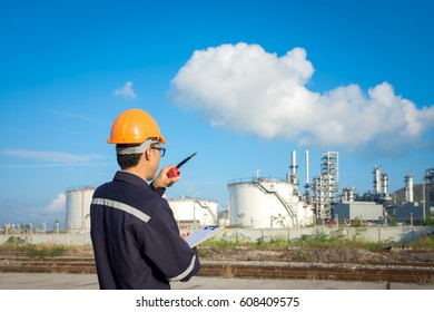 Engineer working in the oil refinery with talking controlling work