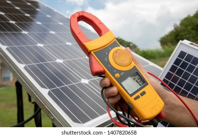 An engineer working on checking equipment in solar power plant. Electrician is using a digital meter to measure the voltage at the power outlet in solar panels