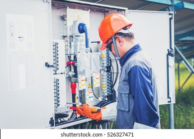 engineer working on checking and maintenance equipment at green energy solar power plant: cheking status inverter