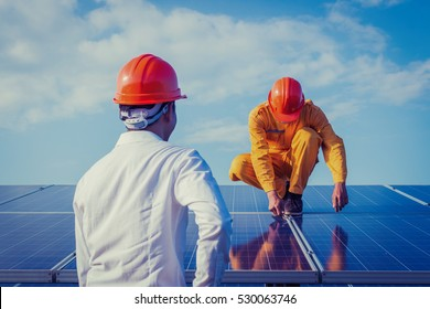 engineer working on checking and maintenance equipment at industry solar power; engineer and technician discussion plan to find problem of solar panel and feeling joyful