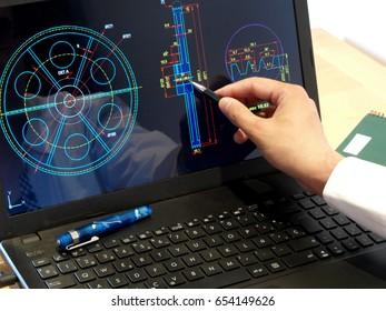 engineer working on computer on mechanical piece design