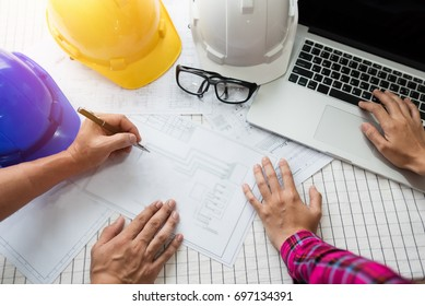 Engineer working on construction project,helmet and laptop on the table.