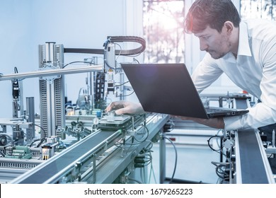 Engineer is working on laptop to program smart factory prototype's automation. Automated car on production line, artificial intelligence in smart manufacturing. Industry 4.0 concept.