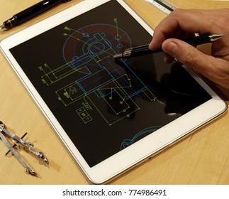engineer working on mechanical piece design blueprint using a tablet computer